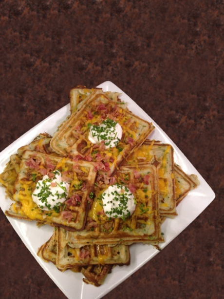 plate of waffles topped with cheese, bacon bits and sour cream